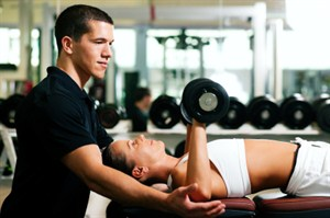 Trainer assisting member with weights